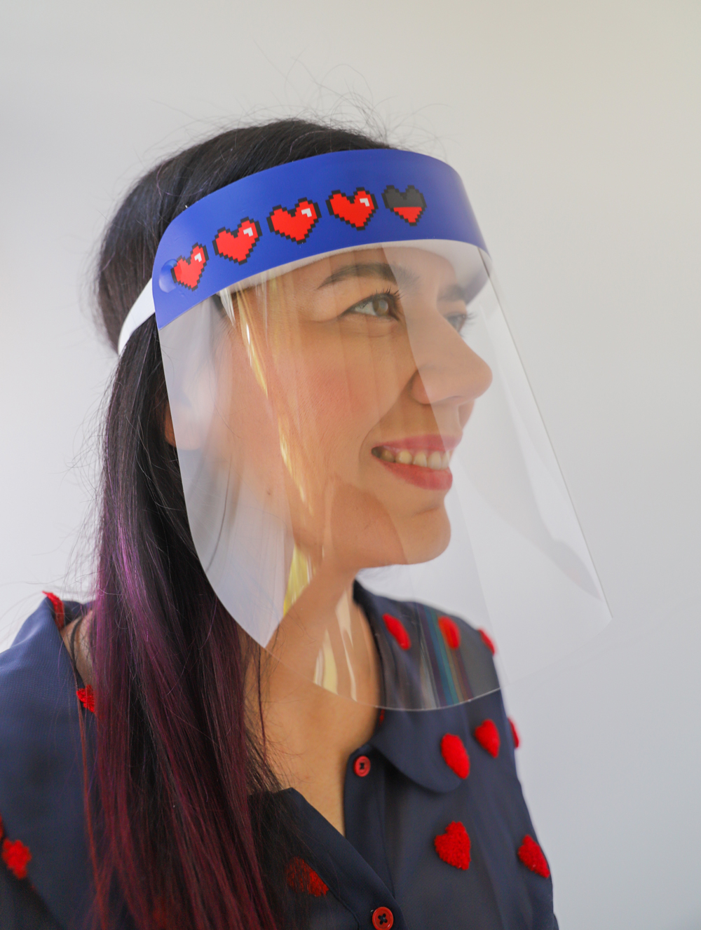 Video Game Hearts Plastic Face Shield protects your eyes, mouth, and nose with style and fun